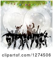 Clipart Of A Silhouetted Crowd Of People Dancing And Jumping Under A Christmas Tree And Lights Over Silver Bokeh And Snowflakes Royalty Free Vector Illustration