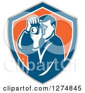 Clipart Of A Retro Male Photographer Taking Pictures In A Taupe Blue White And Orange Shield Royalty Free Vector Illustration by patrimonio