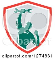 Clipart Of A Retro Mechanic Man Pumping His Fist And A Spanner Wrench In A Red White And Gray Shield Royalty Free Vector Illustration