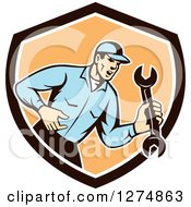Clipart Of A Retro Mechanic Man Shouting And Holding A Spanner Wrench In A Brown White And Orange Shield Royalty Free Vector Illustration