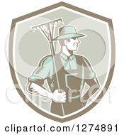 Clipart Of A Retro Woodcut Male Gardener Or Farmer Holding A Rake In A Shield Royalty Free Vector Illustration