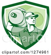 Clipart Of A Retro Male Water Delivery Worker In A Green And White Shield Royalty Free Vector Illustration