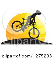 Clipart Of A Silhouetted Female Mountain Biker Jumping Against A Sunset Royalty Free Vector Illustration by Lal Perera