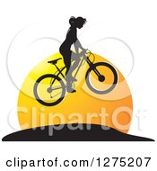 Clipart Of A Black Silhouetted Female Mountain Biker Jumping At Sunset Royalty Free Vector Illustration