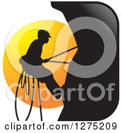 Clipart Of A Silhouetted Male Mountain Climber Against A Sunset Circle Royalty Free Vector Illustration