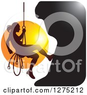 Silhouetted Female Mountain Climber Rapelling Against A Sunset