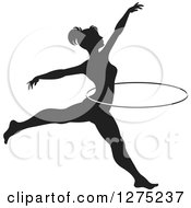 Clipart Of A Black And White Silhouetted Acrobatic Woman Leaping With A Hoop Royalty Free Vector Illustration