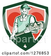 Clipart Of A Retro Male Plumber Holding A Large Monkey Wrench In A Green White And Red Shield Royalty Free Vector Illustration