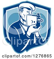 Clipart Of A Retro Male Camera Man Filming In A Blue And White Shield Royalty Free Vector Illustration