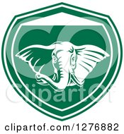 Clipart Of A Retro Tough Elephant In A Green And White Shield Royalty Free Vector Illustration
