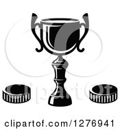 Clipart Of A Black And White Trophy Cup And Hockey Pucks Royalty Free Vector Illustration