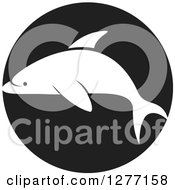 Clipart Of A White Silhouetted Dolphin Over A Black Circle Royalty Free Vector Illustration by Lal Perera