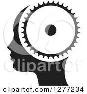Clipart Of A Black And White Silhouetted Womans Head In Profile With A Gear Royalty Free Vector Illustration