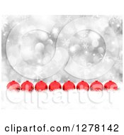 Clipart Of A Christmas Background Of 3d Red Ornaments In A Row In Snow Over Silver Bokeh And Snowflakes Royalty Free Illustration