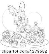 Clipart Of A Black And White Cute Female Bunny Rabbit Decorating A Christmas Cake Royalty Free Vector Illustration