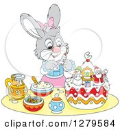 Clipart Of A Cute Gray Girl Bunny Rabbit Decorating A Christmas Cake Royalty Free Vector Illustration by Alex Bannykh