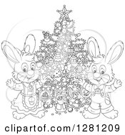 Clipart Of Black And White Cute Festive Rabbits By A Christmas Tree Royalty Free Vector Illustration