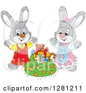 Clipart Of Cute Gray Festive Rabbits By A Christmas Sack Royalty Free Vector Illustration