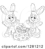 Clipart Of Black And White Cute Gray Festive Rabbits By A Christmas Sack Royalty Free Vector Illustration