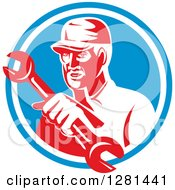 Clipart Of A Retro Male Mechanic Holding Out A Wrench In A Blue And White Circle Royalty Free Vector Illustration