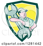 Clipart Of A Retro Cartoon Male Mechanic With His Arm Around A Giant Wrench In A Green White And Yellow Shield Royalty Free Vector Illustration