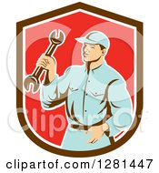 Clipart Of A Retro Male Mechanic Holding A Wrench In A Brown White And Red Shield Royalty Free Vector Illustration