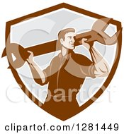 Clipart Of A Retro Male Mechanic With A Giant Wrench On His Shoulders In A Brown White And Gray Shield Royalty Free Vector Illustration