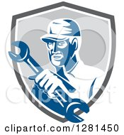 Clipart Of A Retro Male Mechanic Holding Out A Wrench In A Gray Blue And White Shield Royalty Free Vector Illustration