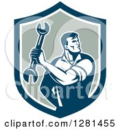 Clipart Of A Retro Muscular Male Mechanic Holding A Wrench In A Shield Royalty Free Vector Illustration