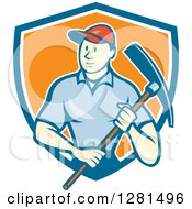 Clipart Of A Retro Cartoon Male Construction Worker Holding A Pickaxe In A Blue White And Orange Shield Royalty Free Vector Illustration