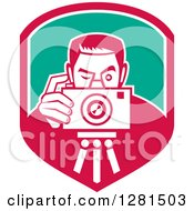 Clipart Of A Retro Male Photographer Taking Pictures On A Tripod In A Pink White And Turquoise Shield Royalty Free Vector Illustration