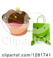 Clipart Of A 3d Happy Green Shopping Or Gift Bag Character Holding Up A Chocolate Frosted Cupcake Royalty Free Illustration
