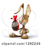 Clipart Of A 3d Brown Bunny Rabbit Facing Left And Holding A Chocolate Easter Egg Royalty Free Illustration