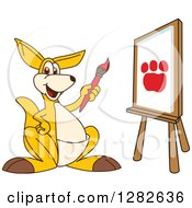 Clipart Of A Happy Kangaroo School Mascot Character Painting A Paw Print On An Art Canvas Royalty Free Vector Illustration by Toons4Biz