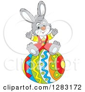 Clipart Of A Happy Gray Easter Bunny Rabbit Cheering On A Giant Egg Royalty Free Vector Illustration