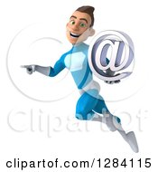Clipart Of A 3d Young Brunette White Male Super Hero In A Blue Suit Facing Left Pointing Flying And Holding An Email Arobase At Symbol Royalty Free Vector Illustration by Julos