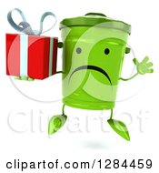 Clipart Of A 3d Unhappy Recycle Bin Character Jumping And Holding A Gift Royalty Free Illustration