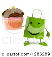 Clipart Of A 3d Happy Green Shopping Or Gift Bag Character Holding A Chocolate Frosted Cupcake Royalty Free Illustration