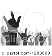 Clipart Of A Silhouetted Grayscale Music Fan Crowd Of Hands Gesturing Rock On Royalty Free Vector Illustration by BNP Design Studio