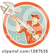 Clipart Of A Retro Cartoon Male Mechanic Holding An Adjustable Wrench In An Orange White And Pastel Green Circle Royalty Free Vector Illustration