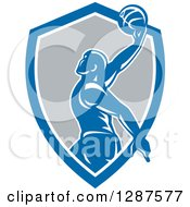 Clipart Of A Retro Silhouetted Basketball Player Doing A Layup In A Blue White And Gray Shield Royalty Free Vector Illustration