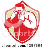 Clipart Of A Retro Male Photographer Taking Pictures In A Red White And Green Shield Royalty Free Vector Illustration by patrimonio