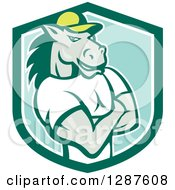 Clipart Of A Cartoon Casual Muscular Horse Man With Folded Arms In A Green Turquoise And White Shield Royalty Free Vector Illustration