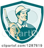 Clipart Of A Retro Gas Station Attendant Jockey Holding A Nozzle In A Turquoise White And Blue Shield Royalty Free Vector Illustration by patrimonio