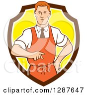 Clipart Of A Retro Cartoon Red Haired White Male Chef Wearing An Apron And Pointing In A Brown White And Yellow Shield Royalty Free Vector Illustration