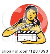 Clipart Of A Retro Female Asian Film Crew Worker Holding A Clapper Over An Orange Circle Royalty Free Vector Illustration