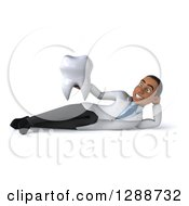 Clipart Of A 3d Young Black Male Doctor Resting On His Side And Holding A Tooth Royalty Free Illustration