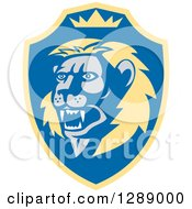 Clipart Of A Retro Roaring Lion Head And Crown In A Yellow And Blue Shield Royalty Free Vector Illustration
