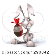 Clipart Of A 3d White Bunny Rabbit Facing To The Left And Holding A Chocolate Easter Egg Royalty Free Illustration by Julos