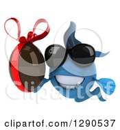 Clipart Of A 3d Happy Blue Fish Wearing Sunglasses And Holding A Chocolate Easter Egg Royalty Free Illustration